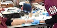 Allied Health Student Poking Another Student With A Needle