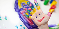 finger-painted face on child hand